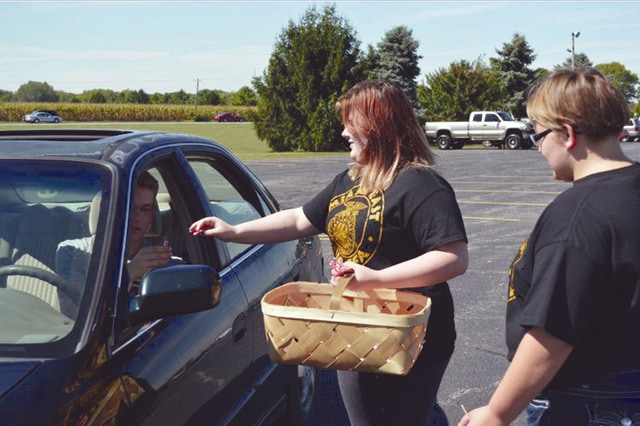 """Provided photo FFA member Caitlin Fryman (left) and Aly Jordan (right) gives a """"Smartie"""" to Nathan Teeters for wearing his seatbelt."""