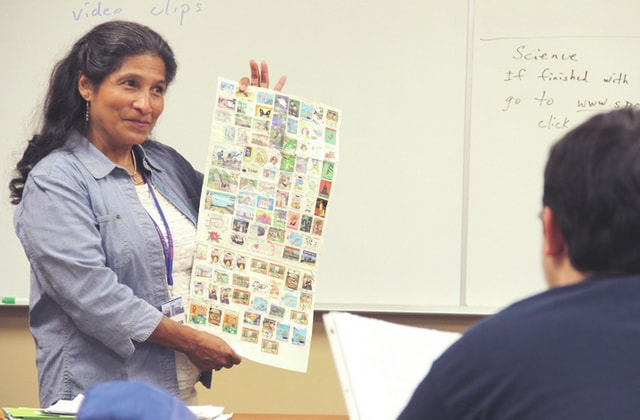 Originally from Honduras, Sonia Haines, left, shows Sue Hahn's students in her American Government class at Upper Valley Career Center 100 Honduran stamps that she has collected over the years. Haines visited Hahn's class last Friday to share her journey in becoming a legalized American citizen.