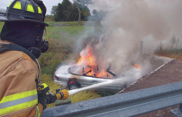 Casstown firefighter Kyle Magato attacks the fire in a burning car on Hufford Road in Elizabeth Township yesterday, after the car went off the road and crashed into a bridge. The driver, who had a fractured ankle and could not walk, was pulled from the car by 16-year-old Jordan Crawford.