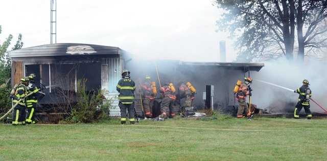 Mike Ullery | Civitas Media Firefighters battle a mobile home fire on Johnson Road, south of Pleasant Hill, on Saturday morning.