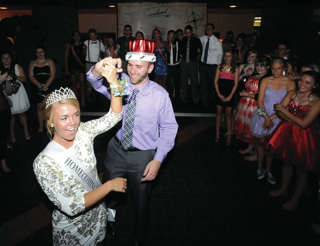 Mike Ullery | Daily Call Piqua homecoming king, Jack Schmiesing, dances with queen Liz Duer, as the homecoming court, and students look on during Saturday's Piqua High School homecoming dance at the high school. Duer was crowned during Friday's football game and Schmiesing during the dance.