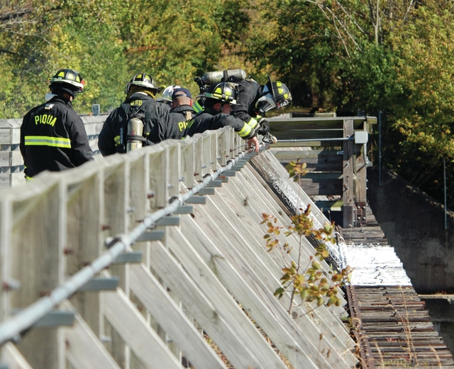 Piqua firefighters extinguish a fire on the bike path bridge across the Great Miami River on Sunday afternoon. They responded to the scene at approximately 2:45 p.m. and used a combination of water and foam to reach the flames which were as much in and under the bridge as on it. South Main Street was closed between Wood and Water Streets while firefighters worked the blaze. Piqua fire units cleared the scene at 4 p.m but the bridge will be closed until further notice. The cause of the fire is not yet known. This not the first time the bridge has caught fire. The last time was in June of 2012, causing significant damage and prompting the bridge to be closed for several months.