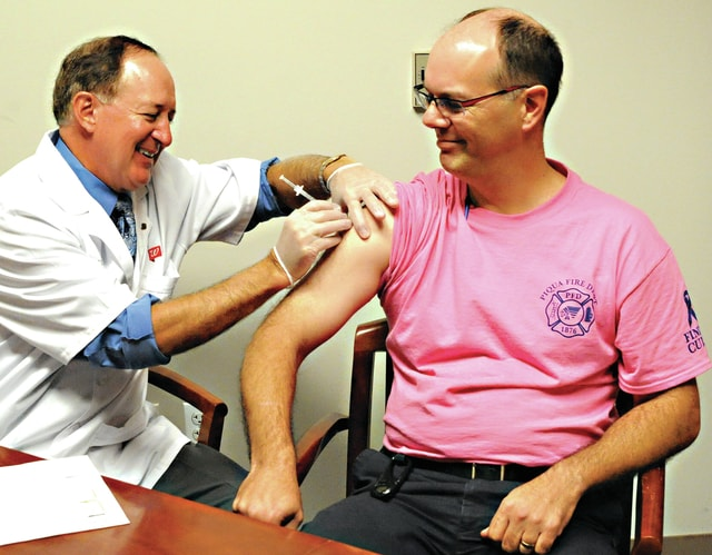 Mike Ullery | Daily Call Piqua firefighter Bob Bloom, right, receives a flu shot from Walgreen's pharmacist Kim Laughlin at the Piqua City Building on Tuesday. Walgreen's was on-site to give flu shots to any city employee who wished to have one.