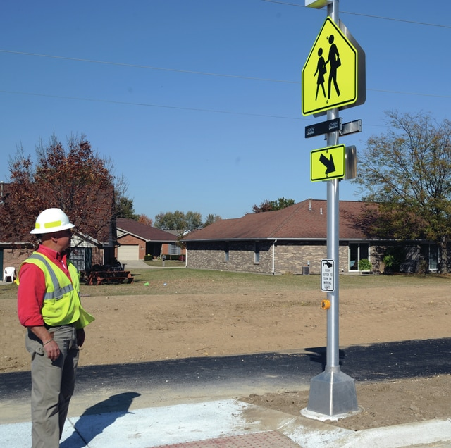 Mike Ullery | Daily Call Bob Graeser of the city of Piqua inspects the first Rectangular Rapid Flash Beacon crossing signal to be installed in the city, on County Road 25-A near Piqua High School, early this week.