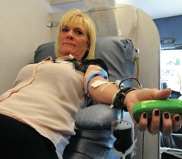 Mike Ullery | Daily Call Julie Jordan of Piqua donates blood at U.S. Bank in Piqua on Monday as part of the Piqua/Troy Community Blood Drive Challenge. The winner of this year's challenge will receive a $1000 award for their school. The winner will be announced at Friday's Piqua vs. Troy football game at Troy Memorial Stadium.