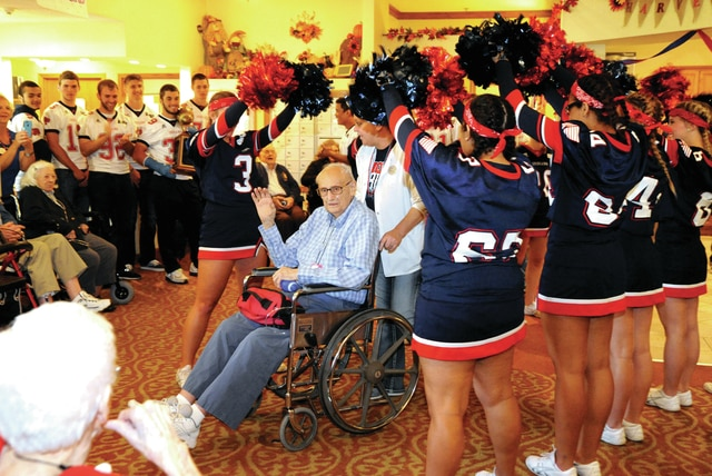 "Mike Ullery | Daily Call Piqua Indians cheerleaders make a tunnel as they recognize Howard ""Howdy"" Reed during a pep rally at Brookdale Assisted Living facility in Piqua on Thursday. Reed's mother was a Troy High School graduate. Young Reed lived in Troy until he was 12, then moved to Piqua. He played center for the Indians in the 1942 Piqua vs. Troy game. The game was played ""shortly after noon on Thanksgiving Day,"" and ended in a 7-7 tie, one of only six ties in the history of the oldest football rivalry in Ohio. Reed went on to work for 33 years with Piqua City Schools, 16 years teaching at Bennett followed by 17 at Piqua High School, most of those as assistant principal. As the pep rally was winding down, Reed, who retired in 1984, said in a strong voice, ""I have one more thing to say. BEAT TROY!"""