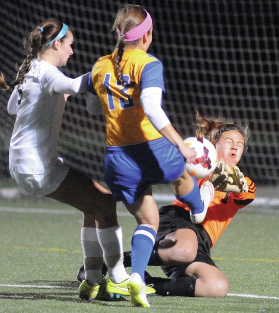 Mike Ullery | Daily Call Sarah Fuller chips a ball over CCD keeper Olivia Robinson, which led to a score by Grace Olding Thursday at Monroe High School.