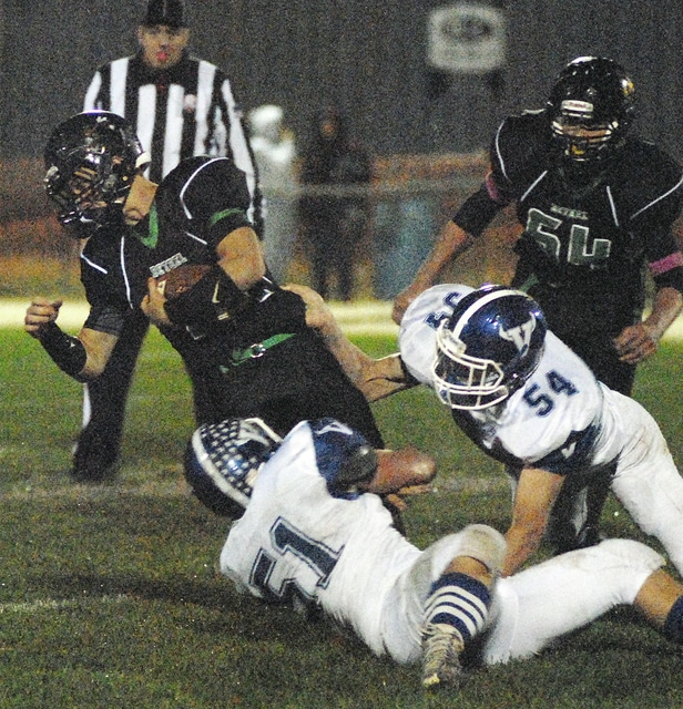 Anthony Weber | Troy Daily News Bethel's Matt First (14) is stopped by Miami East's Caden Hellyer (51) and Michael Werling (54) Friday at Bethel.