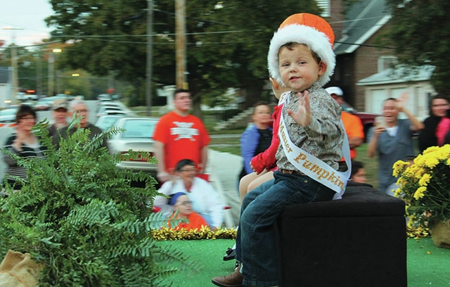 Little Master Pumpkin Brawley Sides waves to the crowd Thursday evening during the 2015 Bradford Pumpkin Show parade. He is the son of Cassie Sascher and Rowdy Sides, of Bradford.