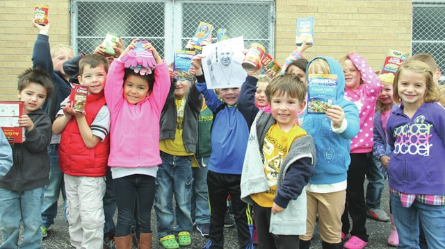 With one child holding a picture of Pope Francis, students from The Center for Early Learning on Friday show off the items they are donating to the Bethany Center. The pope's recent U.S. visit ohas taught students the value of being kind and giving.