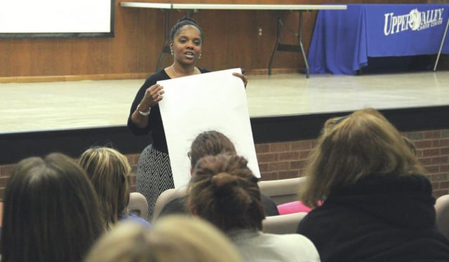 "National speaker and author Nefertiti Bruce Poyner holds a poster board and tells the audience to write down what they believe should go in a child's suitcase on their ""journey through life."" This was one of several activities conducted during Poyner's presentation ""Steps to Support Strength, Security, and Self-Control in Children"" on Wednesday at the Upper Valley Career Center."