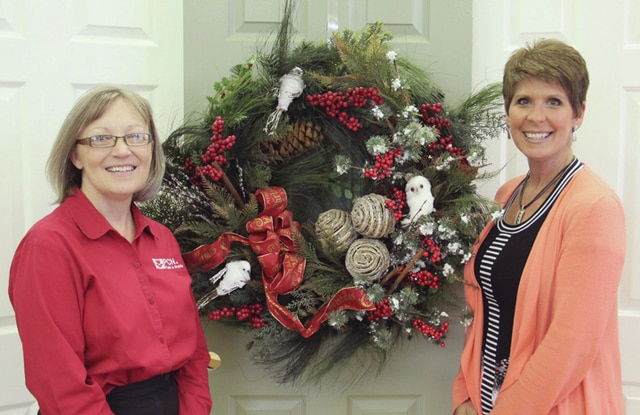 """Ann Hoover, executive director of Piqua Compassion Network, left, and Amy Booher, PCN board member, exhibit one example of a wreath that can be donated for """"The Light of Christmas"""" auction to be held Nov. 12-14 at the Miami Valley Centre Mall. The auction is the major annual fundraiser for the non-profit PCN."""