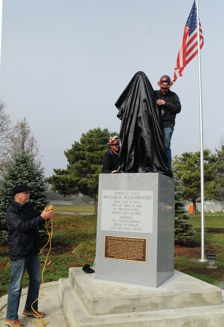 Mike Ullery | Daily Call Sculptor Mike Major, left, and workers from Piqua Steel cover the new statue of William H. Pitsenbarger after it was placed on its pedestal on Wednesday morning at Pitsenbarger Park and Sports Complex. The dedication for the new memorial honoring the 1962 Piqua Central High School graduate, who earned both the Medal of Honor and Air Force Cross in Vietnam, will be held Saturday at 10 a.m. at the park.