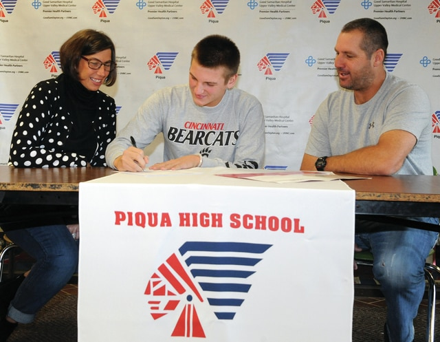 Mike Ullery | Daily Call Piqua senior Ike Karn, center, signs his National Letter of Intent to attend the University of Cincinnati following graduation. Karn is pictured with his mom, Shani and dad, Travis, during the signing ceremony at Piqua High School.