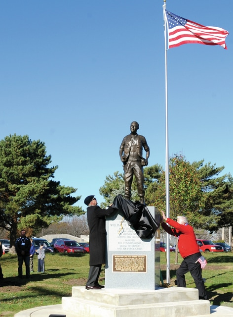 Mike Ullery | Daily Call Sculptor Mike Major, of Urbana, left, and Don Smith, a member of the Friends of Piqua Parks committee, right, and fellow committee member Chuck Peltier, (behind monument), unveil the bronze likeness of Piqua native A1C William H. Pitsenbarger, recipient of the Medal of Honor and Air Force Cross, during ceremonies at the Pitsenbarger Sports Complex on Saturday.