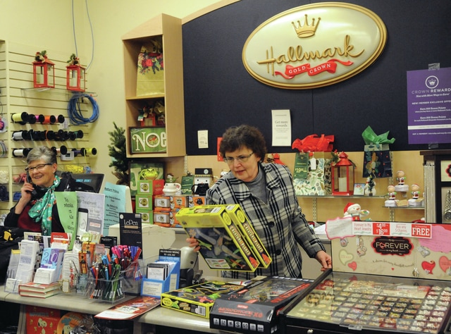 Mike Ullery | Daily Call Manager Mary Beth Barhorst, center, takes care of a customer at the sales counter on Tuesday at the Piqua Readmore's Hallmark Store.