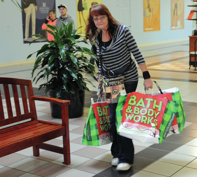 Mike Ullery | Daily Call Vickie Wells carries packages through the Miami Valley Centre Mall on Friday morning. Wells' mother-in-law lives in Piqua and the Salem, IN resident makes the five-hour trip to the mall every year for Black Friday shopping.