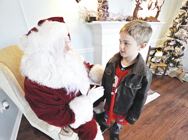 Anthony Weber | Troy Daily News Gavin Miller along with his brother, Devin, stopped by the Santa House to discuss a few things Saturday on Prouty Plaza. The Miller brother's along with their mother, Valerie, were out-and-about during Small Business Saturday in downtown Troy. The Santa House will be opened weekends for several hours throughout the Christmas season.
