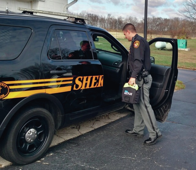 Provided photo | Miami County Sheriff's Office Deputy Nate Jessup places an automated external defibrillator into a sheriff's cruiser last week. The sheriff's office received six AEDs purchased through a grant from the Miami County Foundation.