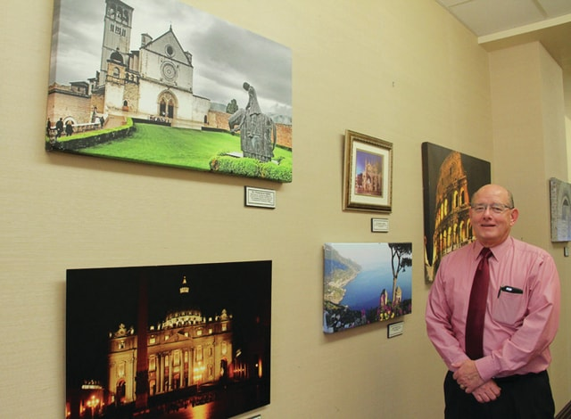 Jerry McGlothen shows some of his favorite photographs of Italy that are on display at the Piqua Public Library through Nov. 30.