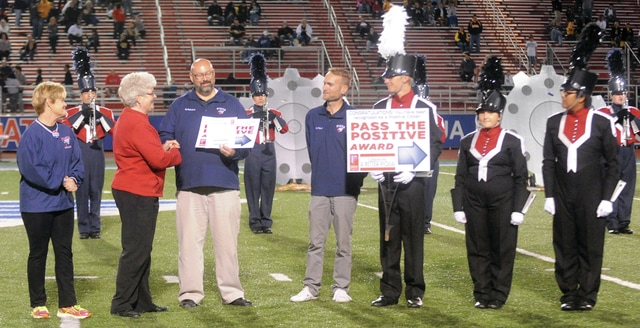 "Mike Ullery | Daily Call Kazy Hinds and Sharon Semanie of Positively Promoting Piqua present a ""Pass the Positive"" award to the Piqua High School Marching Band durin the Piqua vs. Sidney football at Alexander Stadium/Purk Field on October 23, 2015."
