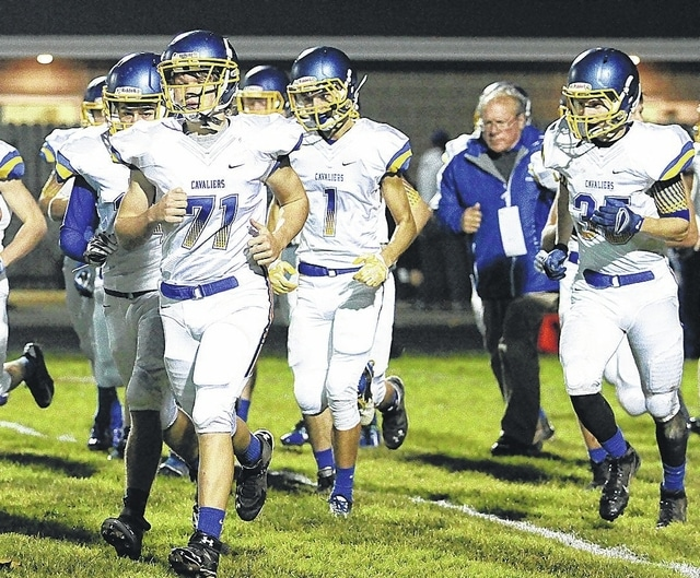 Veteran Lehman head coach Dick Roll heads out on the field in the midst of his players as the Cavs get set to take on Covington last week. They play Fort Recovery Friday in a second-round playoff game.