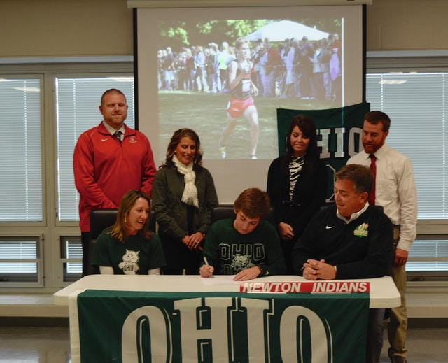 Rob Kiser/Call Photo Brady McBride signed his letter of intent to run for Ohio Univeristy. In front with McBride are his parents Tiffany and Pat McBride. In back are Newton athletic director Gavin Spitler, assistant cross country coach Aubrey Hughes, Newton High School principal Danielle Davis and Newton track and field coach Nick Rhoades.