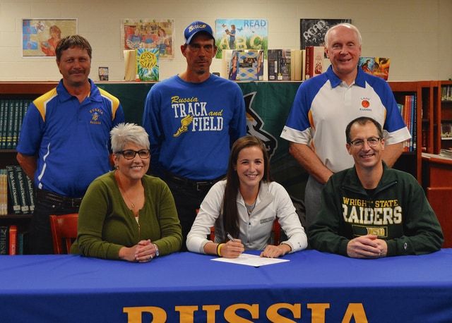 Rob Kiser/Call Photo Russia senior Molly Kearns signs her letter of intent to run cross country for Wright State University. In front with Kearns are her parents Dee and Tim Kearns. In back are Russia track and field coaches Dan Schafer and Brad Heaton and Russia cross country coach Doug Foster.