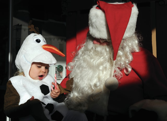 Mike Ullery | Daily Call Olaf, aka, two-year-old Zoe-Lynn Smith, of Piqua, chats with Santa Claus at the Piqua Public Library on Saturday following the annual Christmas Parade through the downtown.