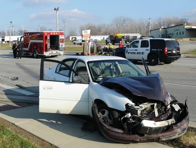 Mike Ullery | Daily Call Piqua police, fire and EMS work the scene of a two-vehicle crash at the intersection of Co. Rd. 25A and Hetzler Road on Monday afternoon. According to police, a minivan that was stopped at the stop sign on Hetzler Road apparently pulled into the path of a southbound car. The vehicles collided, causing the van to turn onto its side, trapping the driver. Firefighters were able to free driver who was transported to Upper Valley Medical Center. The occupants of the car refused treatment at the scene. The crash, which occurred around 2:40 p.m. is under investigation by Piqua police.