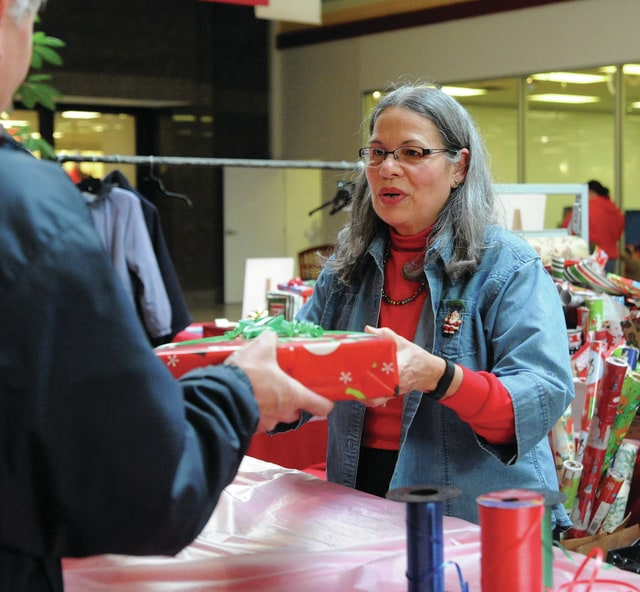 Mike Ullery | Daily Call Brenda Morland, of Sidney hands a wrapped gift to a patron at the Lehman Music Boosters gift-wrapping booth at the Miami Valley Centre Mall on Friday. The booth is a fund-raising project for the music program at Lehman Catholic High School.