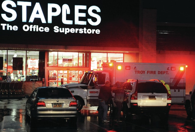 Mike Ullery | Civitas Media Troy Fire Department medics tend to a patient who was seated in the passenger seat of a parked SUV in the parking lot of the Staples store in Troy when part of a sign blew into the vehicle, and through the passenger window, injuring the victim.