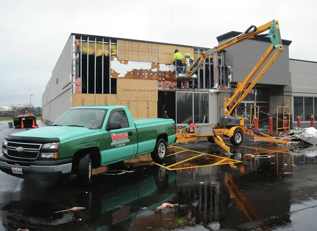 Mike Ullery | Daily Call Crews from Bruns Construction work to board up damage to the former Rex store in the 2000 block of West Main Street in Troy following a round of storms that moved through the area early Sunday morning.