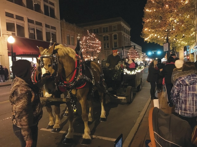 A line stands along Main Street in downtown Piqua, awaiting a turn on a horse-drawn carriage during Mainstreet Piqua's Christmas on the Green event on Friday evening.