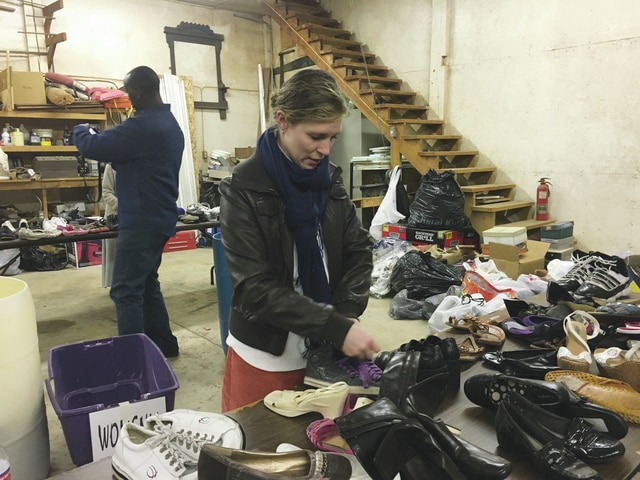 Julie Benedict of Well of Hope America works on tying pairs of shoes together on Monday night to get them ready to be bagged and sent to Kenya.