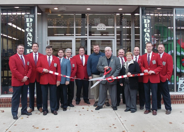 Provided photo The Piqua Area Chamber of Commerce Ambassadors along with Scott Miller, chamber president, conducted a ribbon cutting on Thursday, Dec. 10, 2015 at Dugan's Pawn Shop, 414 N. Main St., Piqua. Cutting the ribbon is owner Doug Arp with his son Andrew Arp, sales manager.