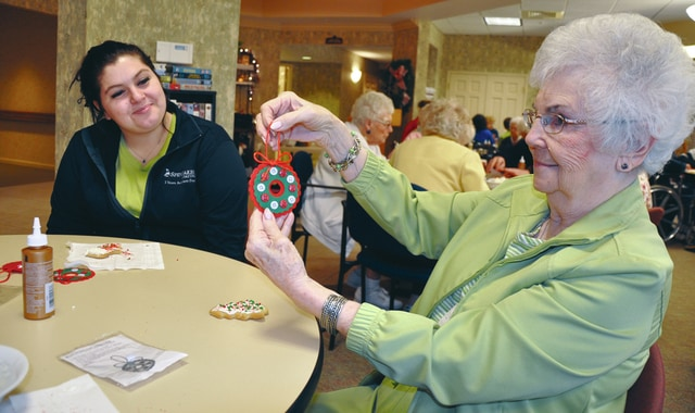 Provided photo Upper Valley Career Center Student Senate members recently spent the day sharing holiday activities and treats with residents at Garbry Ridge in Piqua. Emily Phillips, left, helps make an ornament with Dot Hatcher.