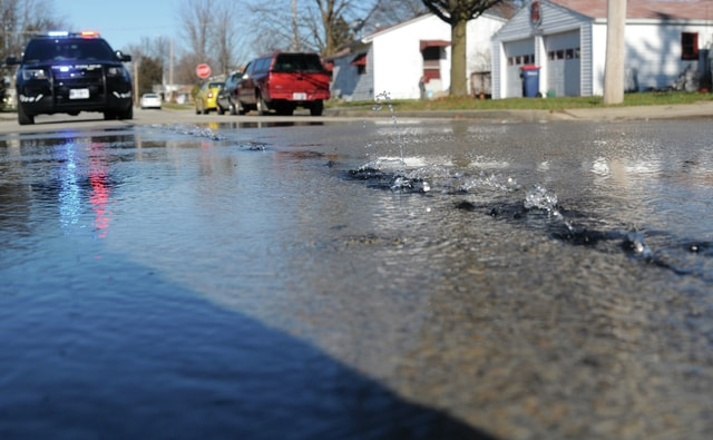 Mike Ullery   Daily Call Tiny fountains of water shoot up from the street on Linden Ave., near Clark Ave. in Piqua, on Tuesday afternoon. A watermain break forced the closure of a portion of the street as crews dug up and repaired the broken line.