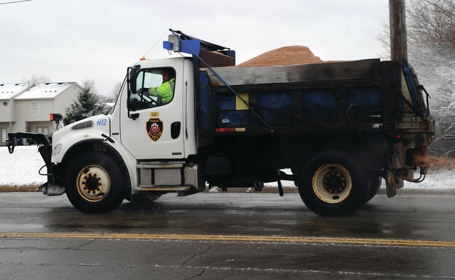 Mike Ullery | Daily Call A Piqua Street Department truck spreads salt on Looney Road, near Piqua High School, on Sunday morning following the season's first snowfall.