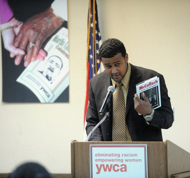Mike Ullery | Daily Call Special guest speaker Shane Carter, a Troy native and executive director of Lincoln Community Center in Troy, references Piqua native and civil rights advocate William McCullach, during his MLK Day address at the Miami County YWCA in Piqua on Monday.