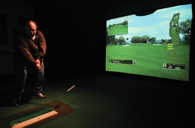 Mike Ullery | Daily Call Mike Emerick hits a shot into the golf simulator at Z's Sports Bar.