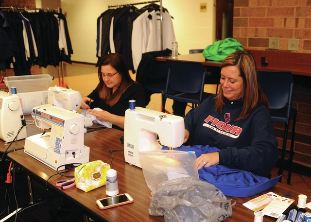 Mike Ullery | Daily Call Choir choir moms Maria Bubp, left, and Misty Iddings, man sewing machines at Piqua High School on Thursday. The group was making alterations to costumes to be worn by members of The Company, adding Velcro closures instead of buttons to make frequent and fast costume changes an easier task.