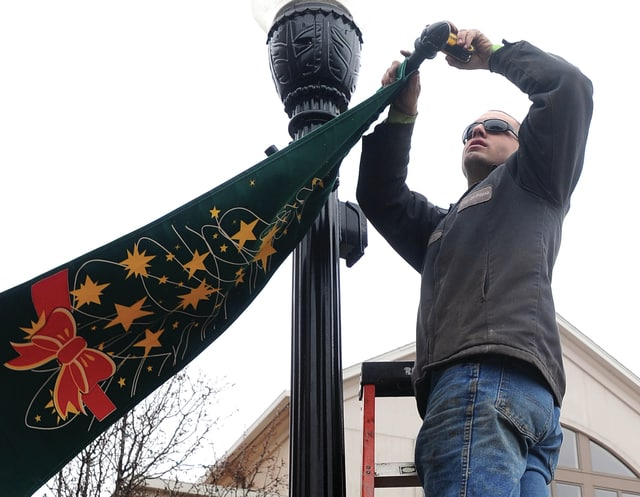 Mike Ullery | Daily Call Piqua City Parks employee Ben Gover removes Christmas holiday banners from downtown light poles on Tuesday afternoon.