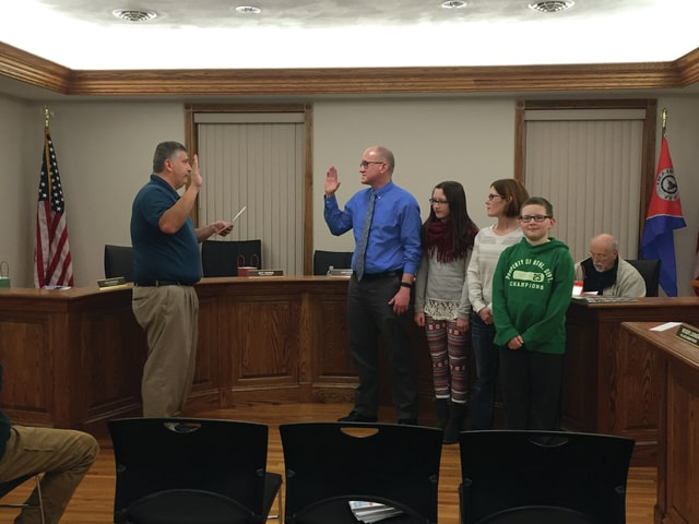 Heather Canan | For the Daily Call Bradford Mayor Don Stump swears in new village council member Bob Daugherty as his wife and children proudly watch him.