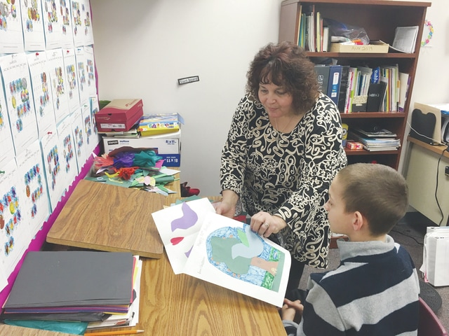 Neurological Education teacher Susan Supinger (left) shows the different birthday cards her students are making for Lucille Sansam, 100-year-old Piqua native. Easton, 12, (right) explains how he made his birthday card.