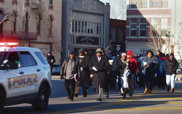 Dave Fornell | Troy Daily News Braving freezing temperatures, a small crowd is escorted through Troy's Public Square in remembrance of the Rev. Dr. Martin Luther King Jr. on Monday.