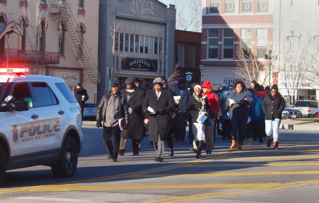 Braving freezing temperatures, a small crowd is escorted through Troy's Public Square in remembrance of Rev. Dr. Martin Luther King Jr. on Monday.