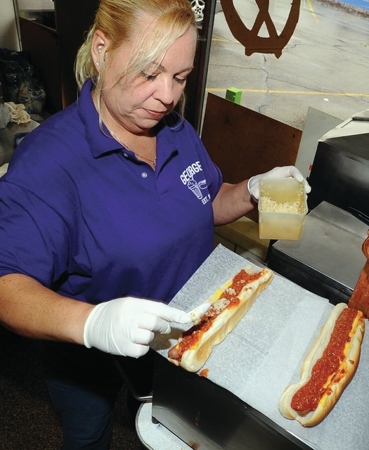 Mike Ullery | Daily Call Shelley Kraft builds a pair of Coney dogs at George's Dairy Bar on Thursday afternoon. In spite of snow and cold, the long-time Piqua restaurant has been doing a brisk business since opening for the season.