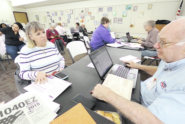 Anthony Weber | Troy Daily News Max Current assists Sandy Lehman with her taxes Friday at the Troy-Miami County Public Library. Taxpayers are able to receive help with their federal, state and school taxes through Tax-Aide at several locations throughout the county.