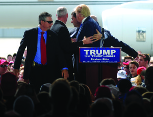 United States Secret Service Agents surround Republican presidential candidate Donald Trump following some commotion in the crowd as he spoke at the Dayton International Airport on March 11, 2016.